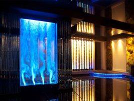 Аквапанель в холле в сочетании со световыми колоннами и фацетными зеркалами